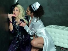 Classy clothed lesbians share a dildo
