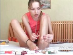 Teenage minx Ivana painting her toe nails in red