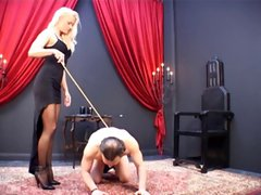 Blonde mistress has her slave on the ground and is caning him