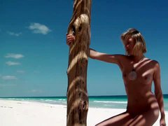 Naked blonde stands tall on the beach