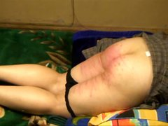 Chubby girl is laid out on the couch and gets her ass caned