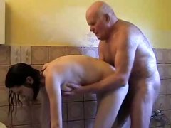 Young brunette helps grandpa take a shower and dries his cock with her mouth